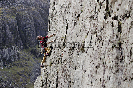 male rock climber scaling rock face