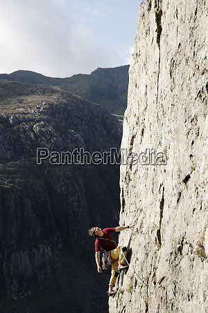 male rock climber scaling large rock