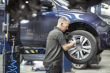 engineer checking brakes in car service