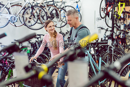 salesman helping customer in bike shop