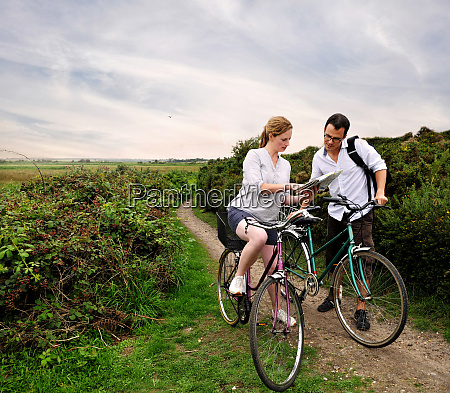 mid adult cycling couple on rural