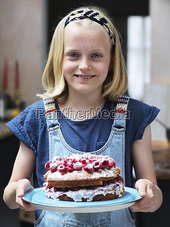 girl baking a cake holding homemade