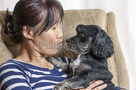 woman and dog in tender moment