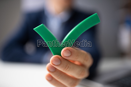 businessperson holding check mark icon