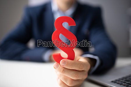 person holding red paragraph sign