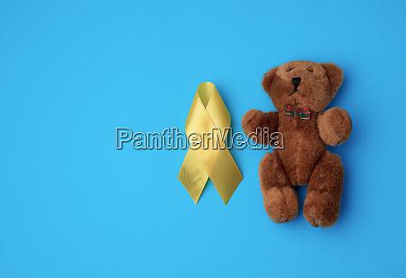 brown teddy bear and yellow silk