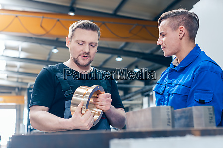 master discussing a workpiece with his