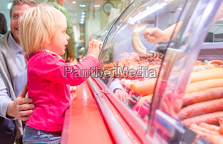 child in front of the meat