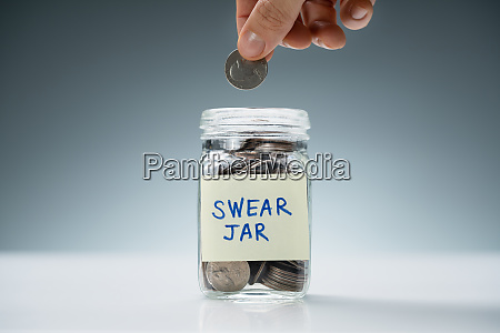 person inserting coin in swear jar