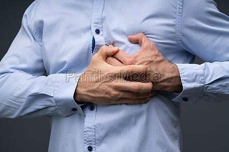 man wearing blue shirt suffering from