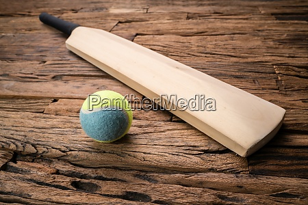 cricket bat and ball on wooden