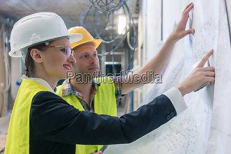 builder and construction worker looking at