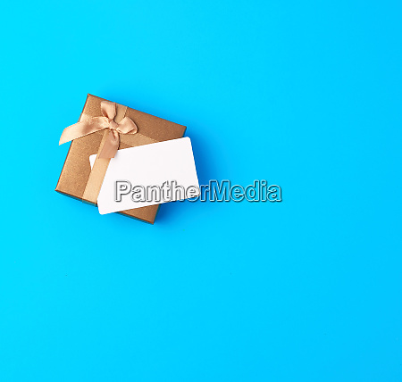 closed brown gift box with bow