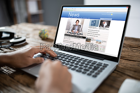 businessman reading news on laptop