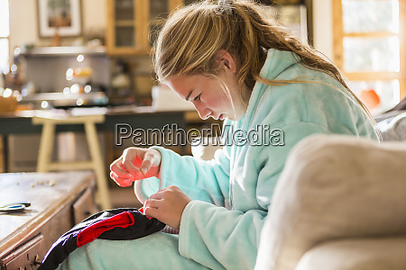 a teenage girl sewing a shirt