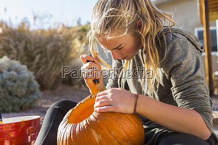a teenage girl carving a pumpkin