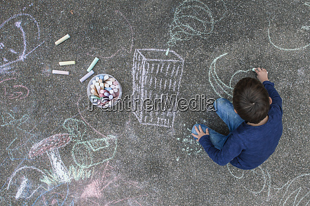 young boy drawing on the sidewalk