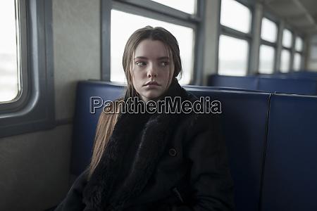 young woman wearing black fur coat