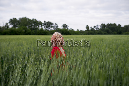 woman with pink hair in wheat
