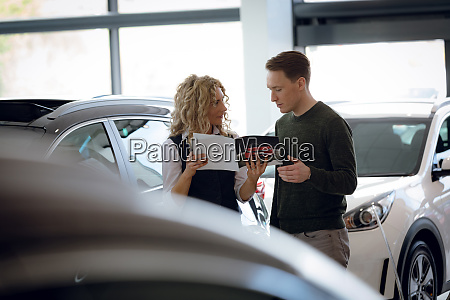 saleswoman holding brochure while standing with
