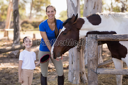 portrait of smiling sister with horse