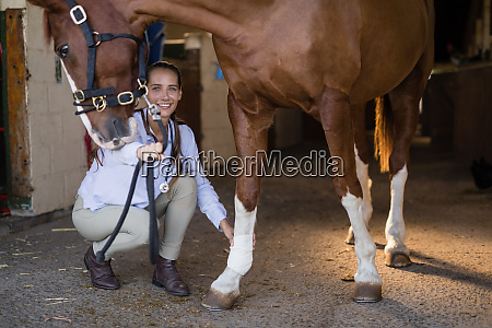female vet examining horse in stable