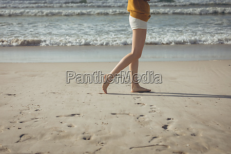woman walking on sand with barefoot