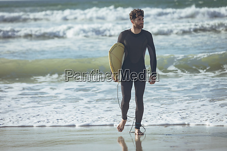 male surfer with a surfboard walking