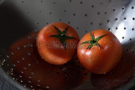 fresh wet tomatoes in strainer