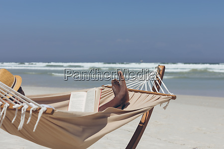 man reading book while relaxing on