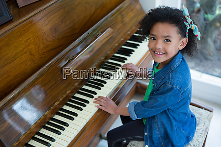 adorable girl playing piano
