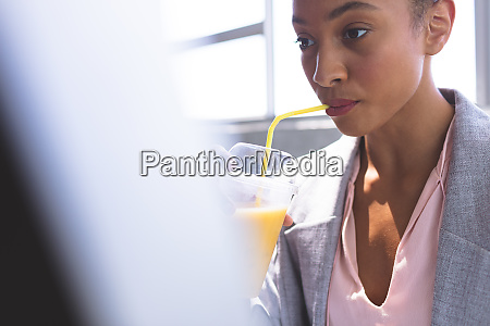 businesswoman having milkshake while working on