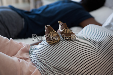 pregnant woman relaxing with baby shoes