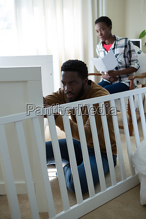 man making cot with pregnant woman
