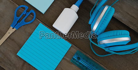 headphone with various stationery on wooden