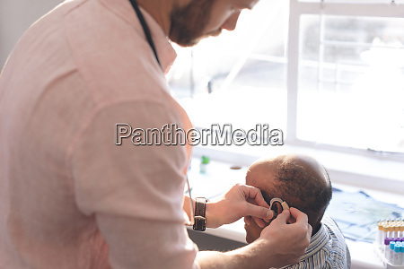 male doctor applying hearing aid to