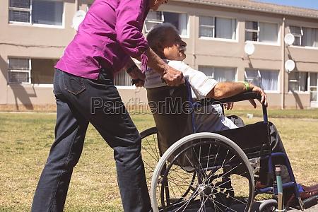 senior woman pushing senior man on