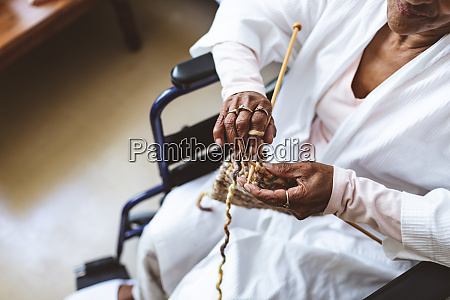 senior woman sitting and knitting with
