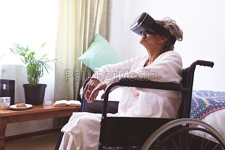 senior woman using virtual realty headset