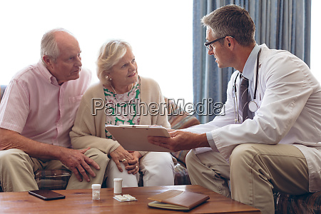 male doctor interacting with senior couple