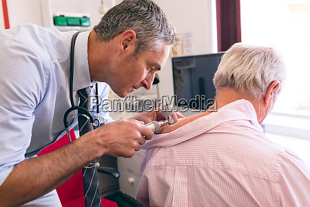 male dermatologist examining senior patient with