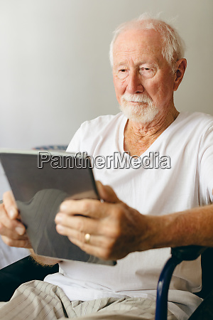 senior male patient using digital tablet