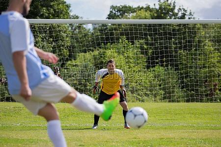 soccer player kicking ball towards goal