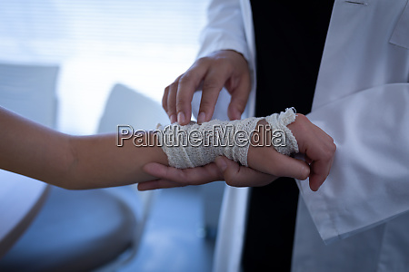 matured female doctor examining girl hand