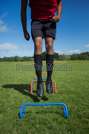 soccer player practicing on obstacle
