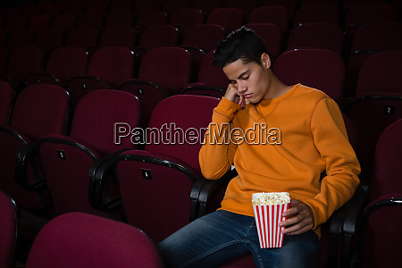 man with popcorn sleeping in theatre
