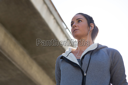 thoughtful female jogger listening to music