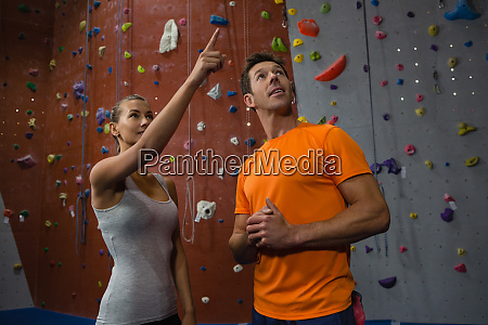 friends talking while standing against climbing