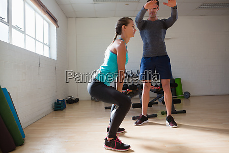 trainer training woman in lifting kettlebells