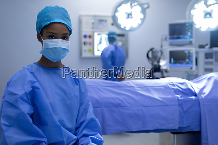 female surgeon sitting with surgical mask